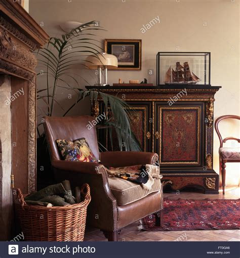 brown leather chair and ornate antique cupboard in old