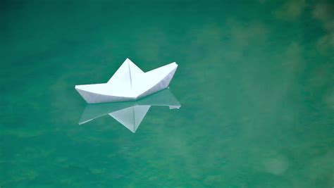 Floating Origami Boat - origami paper boat floats in water stock footage