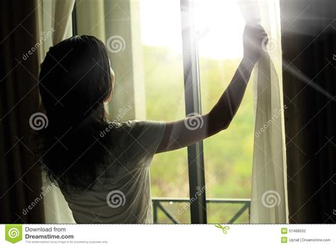 woman opening curtains woman opening curtains in a bedroom stock photo image