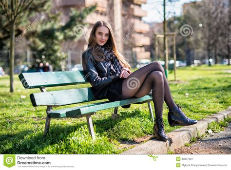 woman on bench beautiful woman sitting on the bench in the park royalty