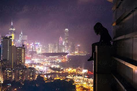 girl sits  edge   building rooftop overlooking hong