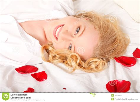 rose petals on bed happy woman in bed with rose petals royalty free stock photo image 18211215