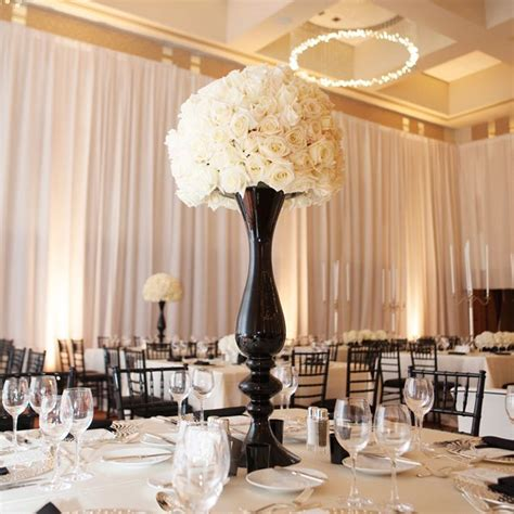 a black vase with white blooms creates a dramatic and