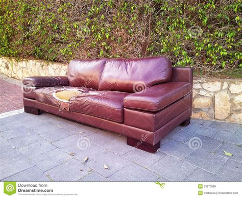 rubber couch ragged leather sofa dumped on a street stock photo image