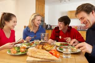 Parents and teen children eating dinner together at home