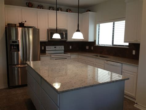 colonial white granite with white cabinets kitchen