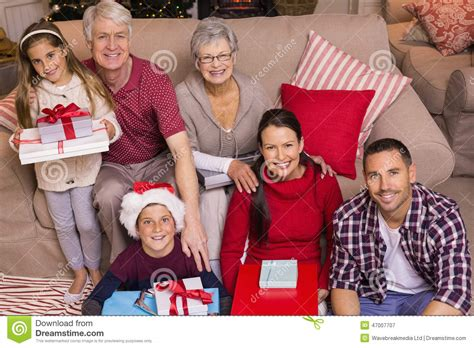 happy family at christmas posing and holding gifts stock
