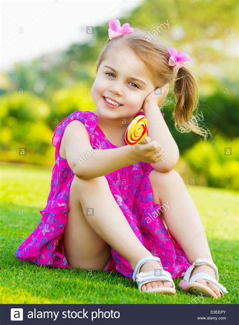 cute little model photo of cute little girl sitting on green grass on