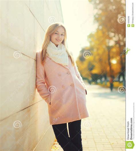 woman smiling wearing pink beautiful young smiling woman wearing a pink coat in