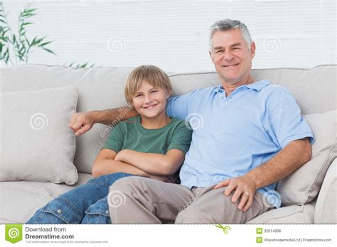 boy on couch young boy sitting on the couch with grandfather royalty
