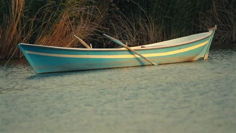 small boat you row beautiful scenery of lake and rows of trees where you can