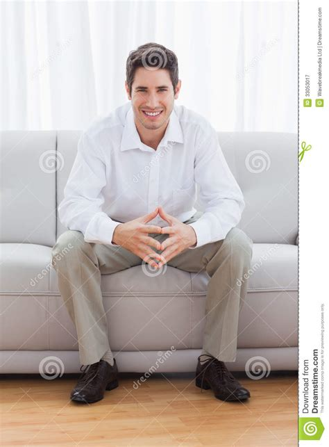 sitting on couch young man sitting on sofa royalty free stock photography