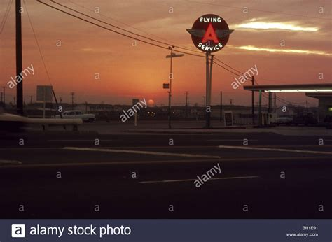 flying with a service flying a service station gasoline sign with wings at sunset stock photo