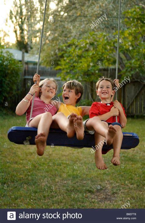 friends swinging three childhood friends on swing in backyard stock photo