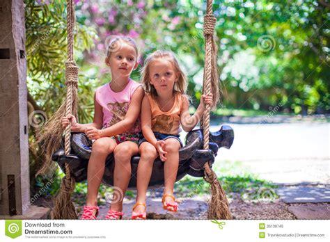 swinging girls little girls swinging in a cozy lovely flowered stock