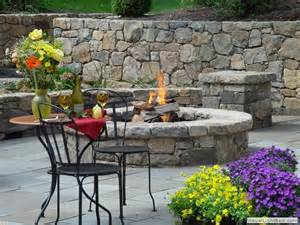 Stone fire pit on bluestone patio with stone sitting walls and stone