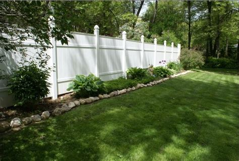 white backyard fence with landscaping landscaping