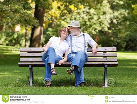 couple on park bench senior couple sitting on a park bench