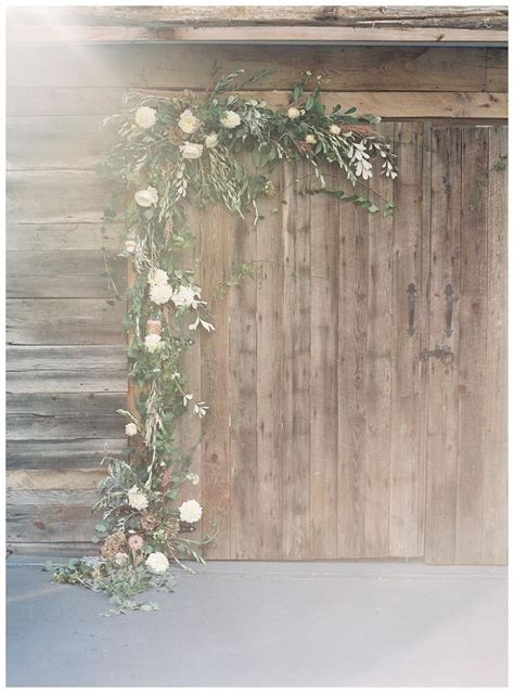 Barn doors with floral garland. Florals by Nectar. Image