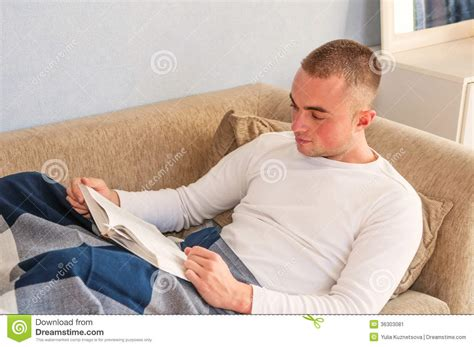 laying couch young man reading a book stock image image 36303081