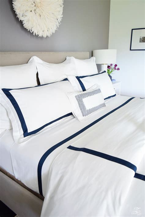 white comforter with blue trim creating a cozy home with the perfect bedding room