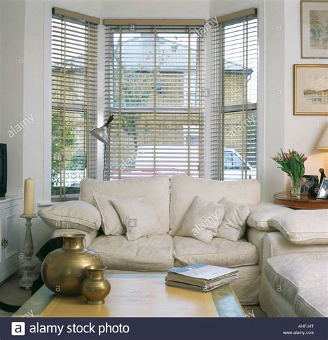 table in front of sofa cream sofa in front of bay window with slatted blind in