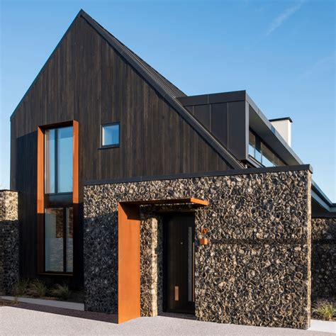 house means rugged flint walls contrast dark cedar gables of house 19