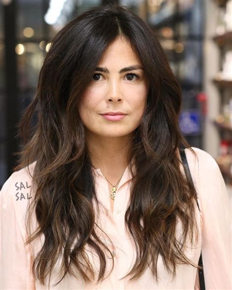 voluminous haircut for straight hair women s long parted layered cut with voluminous bohemian