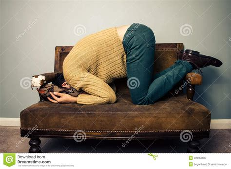 Young Man Burying His Face In Old Sofa Royalty Free Stock