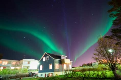 northern lights iceland november back view of blue house with northern lights in early