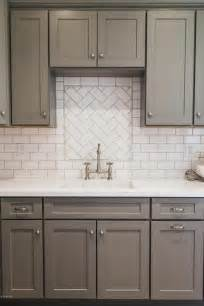 white tile kitchen backsplash gray shaker kitchen cabinets with white subway tile herringbone sink backsplash transitional