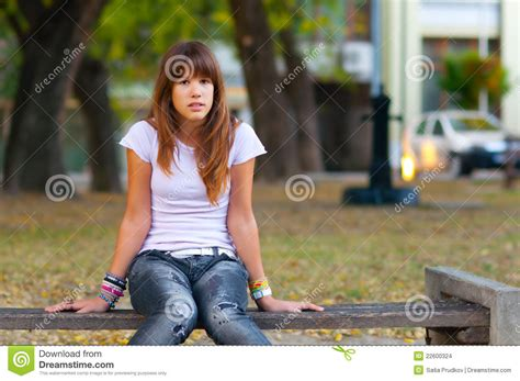 girl sitting on a bench pretty teenage girl sitting on the bench stock images