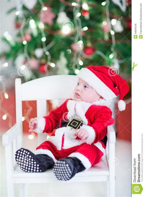 funny newborn baby boy  santa outfit   christmas tree stock photo image