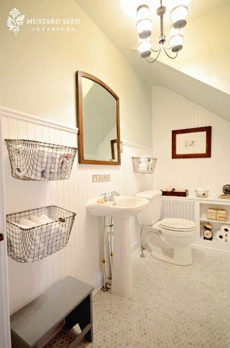 hang baskets on bathroom wall half bath beadboard hex tile warm wood toned mirror