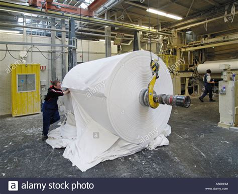 How To Make Paper In Factory - worker trimming a roll of new recycled paper in a
