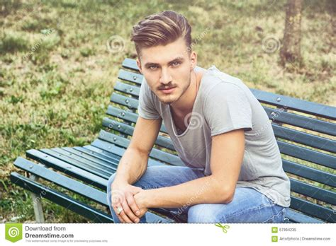 guy sitting on bench handsome blond young man sitting on park bench stock photo