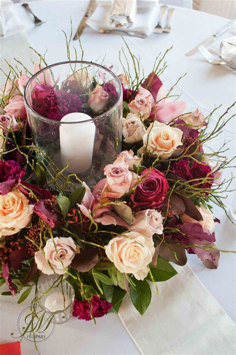 burgundy and wedding table arrangements a floral wreath with incorporated candle in a