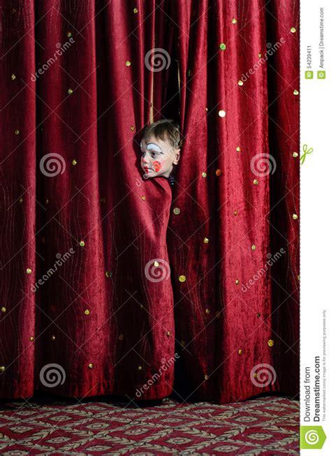 Boy Clown Peering Through Stage Curtains Stock Photo