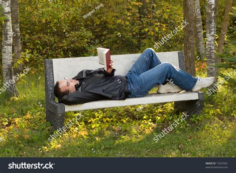 man bench man lying on bench reading book stock photo 17637601
