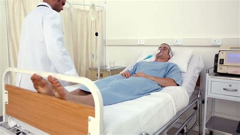doctor checking patient in bed with an oxygen mask in the