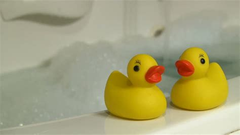 blow up rubber ducky bathtub rubber duckies and bubble bath with woman stirring in hot