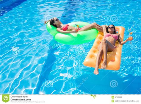 mattress in a pool resting on air mattress in swimming pool stock photo
