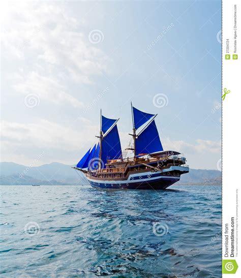 vintage wooden ship  blue sails stock images image