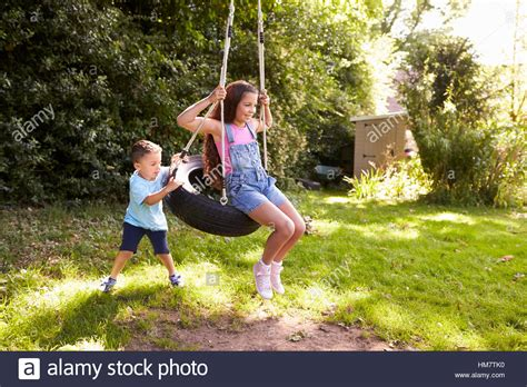 pushing a swing brother pushing sister on tire swing in garden stock photo