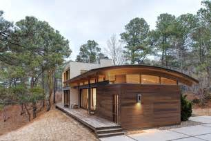 contemporary forest house with curved metal roof modern