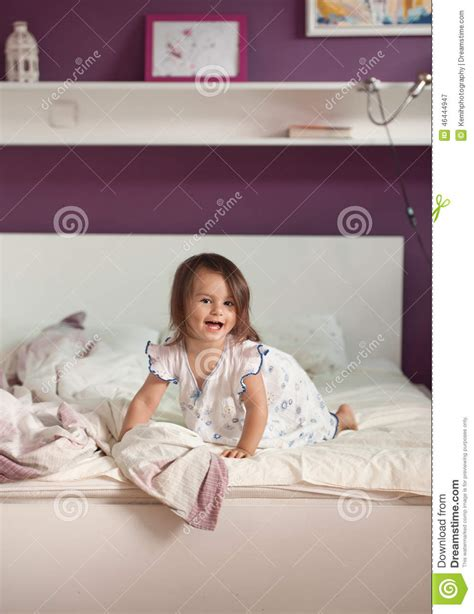 bright morning pillow top beds cute little girl in nightdress on the bed in the morning