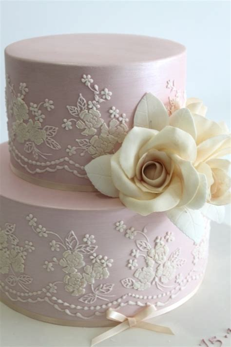 Picture Of a blush wedding cake with white lace, sugar
