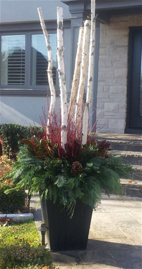 christmas decorating huge stone urns in front of entrance winter container eclectic landscape toronto by earth and sole