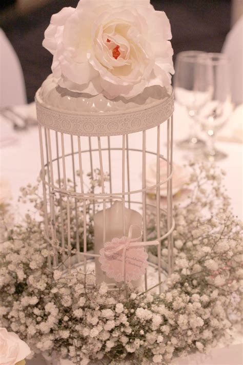 birdcage centerpieces adorned with silk flower and baby