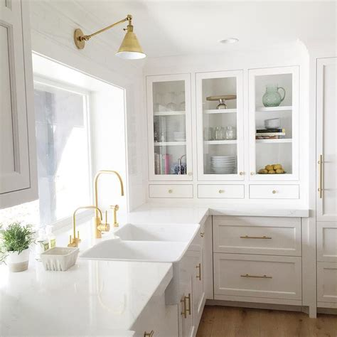 white cabinets with gold hardware dual apron with gold gooseneck faucet transitional
